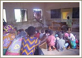 Godoma community members watching a video