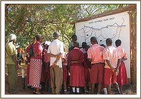 Mwandisha students look at a map of Tsavo
