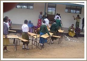 Students carry the donated desks to the classroom