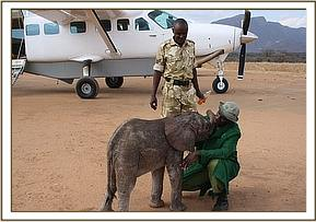 Osman with the tiny baby with the rescue aircraft behind