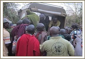 Everyone helps to load the orphan in the vehicle